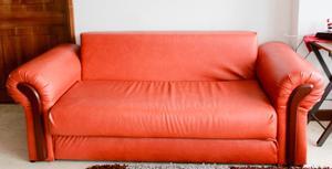Sofá cama anaranjado de cuero.