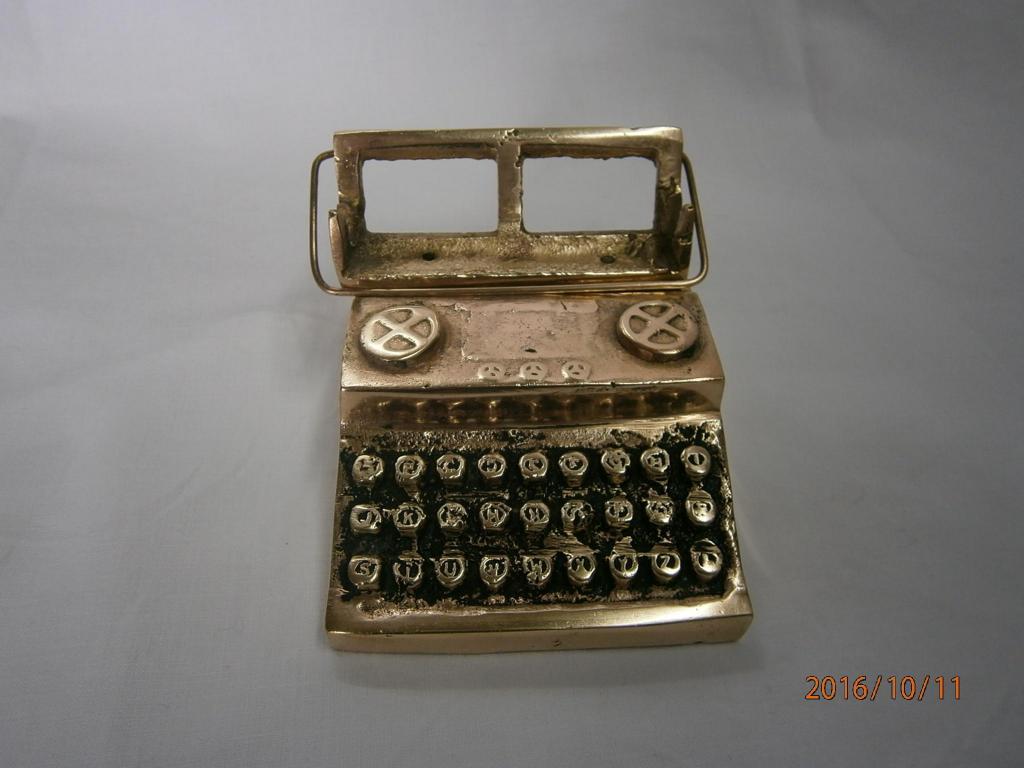 Máquina de escribir pequeña decorativa en bronce.